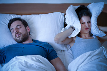 Stressed woman covering ears with a pillow as she is annoyed by the snoring of her boyfriend