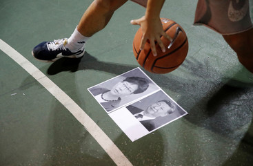 A protester dribbles a basketball over pictures of China's President Xi and Hong Kong Chief Executive Carrie Lam during gathering in support of NBA's Houston Rockets' team general manager Daryl Morey, who sent a tweet backing the pro-democracy movement