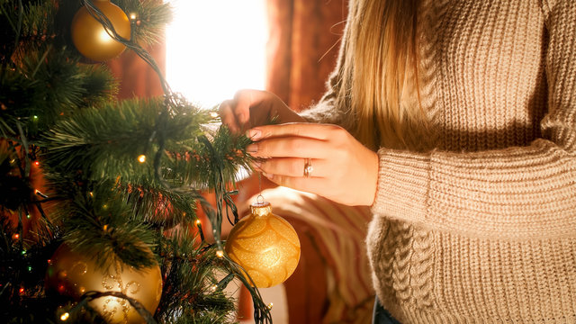 Closeup image of young woman in sweater decorating Christmas tree with golden baubles