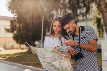 couple tourist in sightseeing in city using paper map and smartphone Wall mural