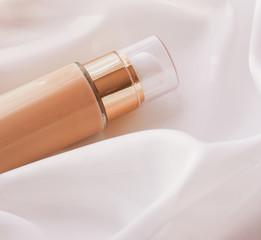 Tonal bb cream bottle make-up fluid foundation base for nude skin color on silk background,...