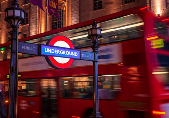 LONDON, UK - JUNE 17, 2013: Illuminated London Underground Tube sign at Piccadilly Circus station entrance with the Double Decker bus moves along the Regent Street in background