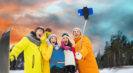 sport, leisure, friendship, technology and people concept - happy friends with snowboards and taking picture by smartphone on selfie stick over winter forest background