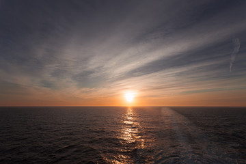 Reflection of dreamy sunset over the sea and wake left by a cruise ship, Adriatic sea, Italy