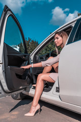 woman behind wheel of car gets out of car, opens door, in summer in city, business lady in suit and high-heeled shoe. Tanned and slim figure of girl.