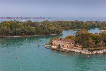 Certosa island with autumn-colored trees and the island of Murano in the background, Venice, Italy