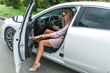 woman package gets out of car summer autumn city. In his hand, mobile phone reads writes message, car sharing rental, pink suit with high-heeled shoes. Tanned and slender girl with long hair.