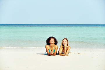 Two smiling women in bikinis suntanning on a tropical beach