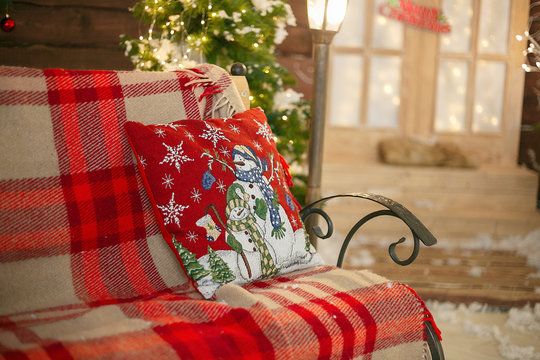 Christmas interior. Bench with plaid on the porch in winter