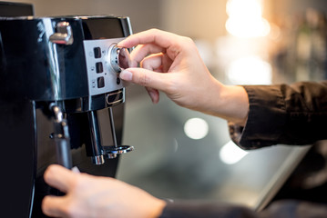 Male barista hand turning button on coffee machine in the kitchen. Making coffee concept