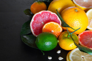 fresh citrus fruits and green leaves on a black background close-up with place for text