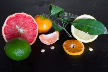 fresh citrus fruits on a black background close-up