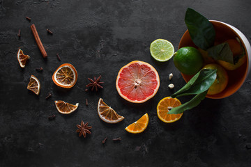 sliced fresh and dry citruses grapefruits, tangerines and lime with cinnamon and star anise on a black background. vitamin c concept