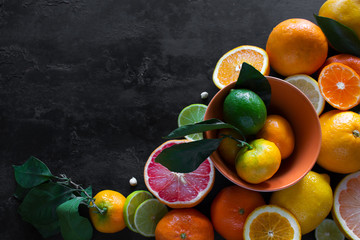 sliced fresh citruses grapefruits, tangerines and lime on a black background with place for text. vitamin c concept