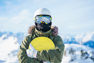 Portrait of man in helmet with snowboard standing on snow resort . Wall mural