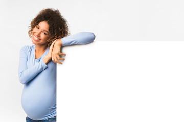 Happy black pregnant woman with billboard, light background