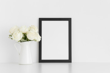 Black frame mockup with a bouquet of white roses in a vase on a white table.Portrait orientation.