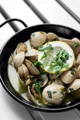 sauteed clams tapas in lemon garlic parsley sauce in spain