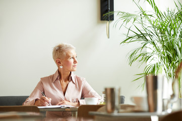 Mature businesswoman with short blond hair looking away while working at the table at office
