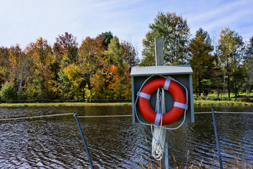 Fall colors across pond with a life ring
