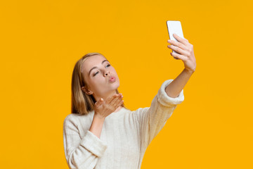 Coquette girl making selfie on smartphone and sending air kiss
