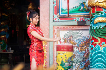 Concept to celebrate Chinese New Year, Vegetarian Festival : Chinese woman in a red cheongsam dress holding incense pay homage to Chinese god at shrine.