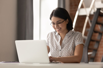 Happy smiling Asian businesswoman in glasses using laptop