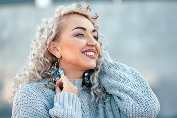 Plus size model with blond curly hair in knitted sweater and silver earrings outdoor