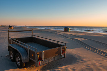 Camper or trailer on sandy sea beach in beautiful sunset with serene seaside in the background