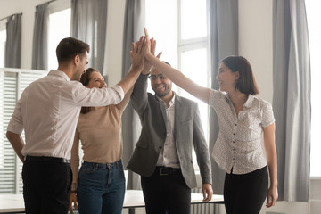 Diverse employees team giving high five, celebrating successful deal