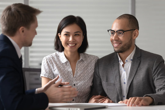 Manager realtor banker consulting happy diverse young couple at meeting