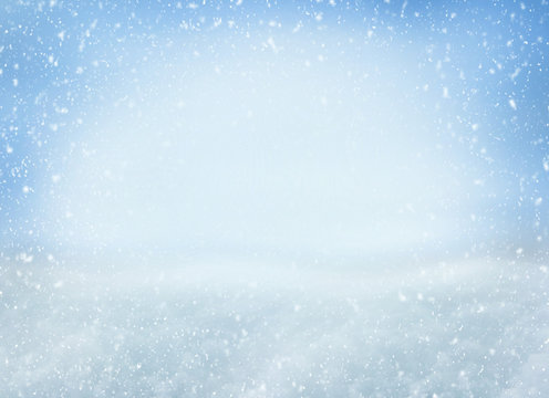 Winter Christmas background with falling snowflakes on blue background. Background for design with copy space