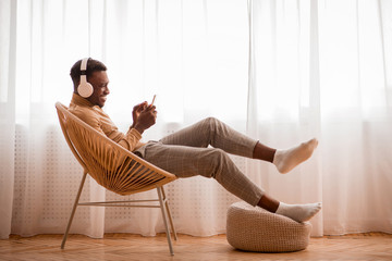 Fotorolgordijn Ontspanning Afro Guy In Headphones Using Smartphone Sitting On Chair Indoor
