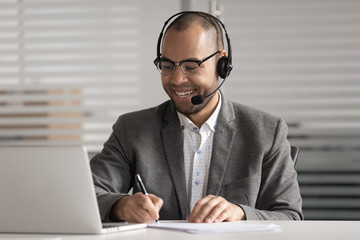 Happy African American employee in headset making notes, using laptop