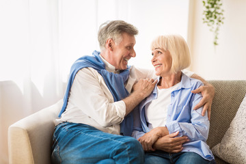 Excited senior couple talking and relaxing at home