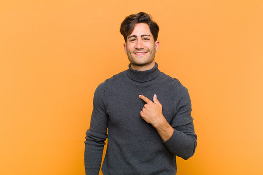 young handsome man looking happy, proud and surprised, cheerfully pointing to self, feeling confident and lofty against orange background