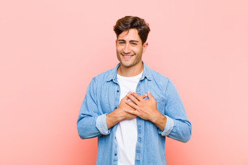young handsome man feeling romantic, happy and in love, smiling cheerfully and holding hands close to heart against pink background