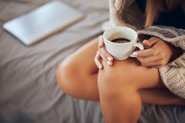Cropped image of caucasian woman in sweater holding cup of coffee while sitting on bed in bedroom.