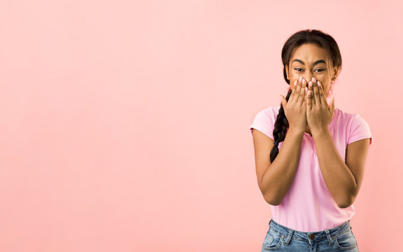 Shocked woman covering her mouth with hands, pink background