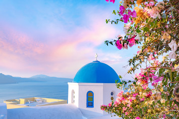 Beautiful Oia town on Santorini island, Greece. Traditional white architecture and greek orthodox churches with blue domes over the Caldera, Aegean sea.