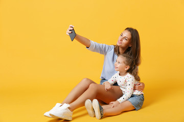Woman doing selfie shot have fun with cute child baby girl 4-5 years old. Mommy little kid daughter isolated on yellow background studio portrait. Mother's Day love family parenthood childhood concept
