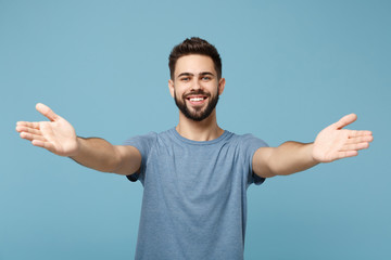 Young smiling handsome man in casual clothes posing isolated on blue wall background, studio portrait. People sincere emotions lifestyle concept. Mock up copy space. Standing with outstretched hands.