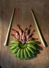fresh green tiny bananas with lemongrass and wilted hibiscus flowers on wooden table
