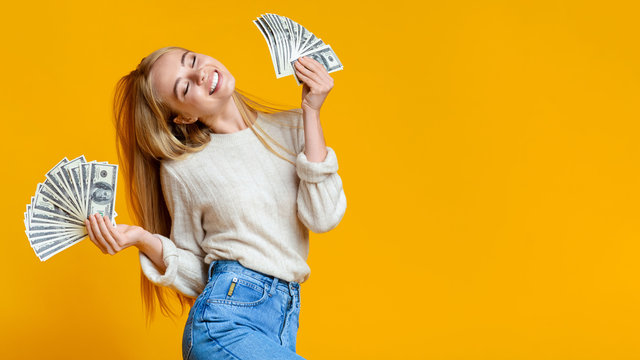 Blissful millennial girl holding lots of money and enjoying success