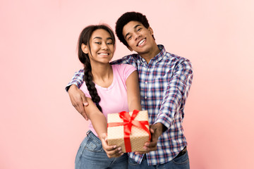 Happy young couple stretching present box to camera