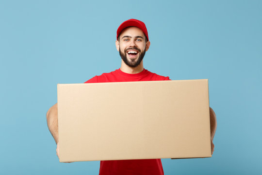 Delivery man in red uniform isolated on blue background, studio portrait. Male employee in cap t-shirt print working as courier dealer hold empty cardboard box. Service concept. Mock up copy space.