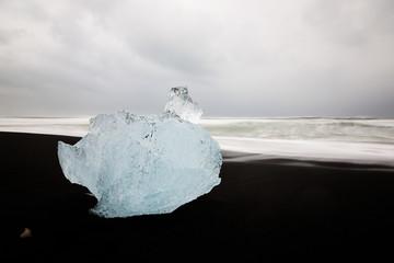 Icebergs sit on black sand Diamond Beach, Jokulsarlon, in the Arctic, Iceland, polished and glistening like jewels.