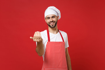Young bearded male chef cook or baker man in striped apron white t-shirt toque chefs hat posing isolated on red background. Cooking food concept. Mock up copy space. Doing gesture like says come here.