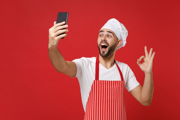 Excited young chef cook or baker man in striped apron toque chefs hat isolated on red wall background. Cooking food concept. Mock up copy space. Doing selfie shot on mobile phone, showing OK gesture.