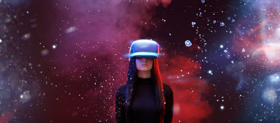 Beautiful woman with flowing hair in futuristic dress over dark space magic background. Girl in glasses of virtual reality. Augmented reality, game, future technology concept. VR.